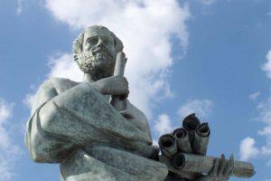 Eine Aristoteles-Statue mit blauem Himmel im Hintergrund.