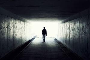 Eine Person läuft aus einem dunkeln Tunnel heraus, beim Ausgang kann man nur helles Licht erkennen.