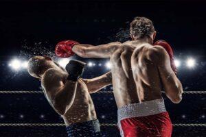 Im Boxring schlägt ein Boxer dem anderen ins Auge.