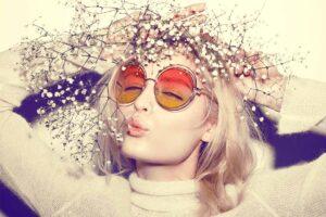 Eine Frau mit Hippie-Brille und Blumen