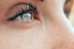 Fokus auf die Augen und Wimpern einer Frau, die in den Himmel schaut.
