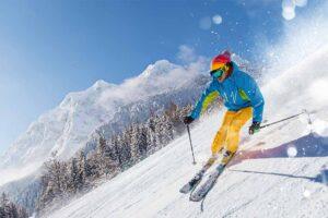 Eine Skifahrer fährt die steile Piste herunter.