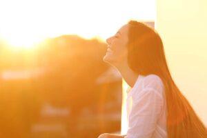 Eine Frau auf dem Balkon genießt die abendlichen Sonnenstrahlen.