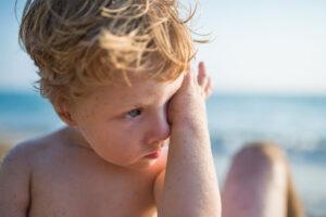 Ein kleiner Junge sitzt im Sand am Meer und reibt sich das Auge.