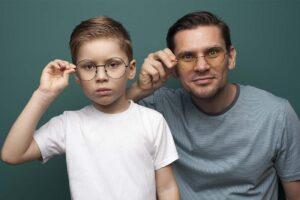 Vater und Sohn schauen in die Kamera, beide tragen eine Brille.