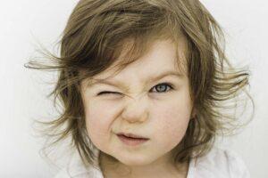 Ein kleines Mädchen kneift ein Auge zusammen.