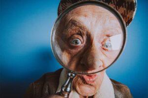 Ein alter Mann schaut durch eine Lupe.