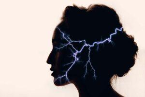 In der Silhouette eines Frauenkopfs sind Blitze zu sehen.