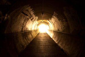Blick aus einem dunklen Tunnel Richtung Ausgang und Licht.