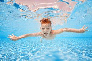 Ein Junge taucht mit offenen Augen in einem Pool.