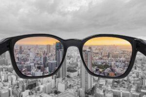 Beim Blick durch die Brille ist der Sonnenuntergang rötlich, außen herum grau.