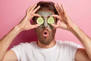 Ein Mann mit Gesichtsmaske hält sich zwei Gurken vor die Augen.