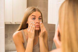 Eine Frau sieht sich im Spiegel an und untersucht ihre Augen.