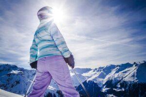 Ein Skifahrer blickt auf die schneebedeckten Berge, die Sonne scheint.