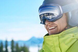 Ein Skifahrer mit Skibrille blickt auf die schneebedeckte Landschaft.