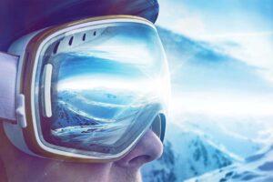 Seitliches Profil eines Skifahrers, in dessen Skibrille sich die Berge spiegel.