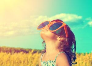 Ein kleines Mädchen mit viel zu großer Sonnenbrille schaut Richtung Sonne.