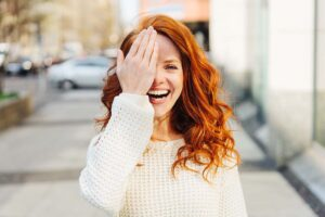 Eine rothaarige Frau auf der Straße hält sich mit der Hand ein Auge zu.