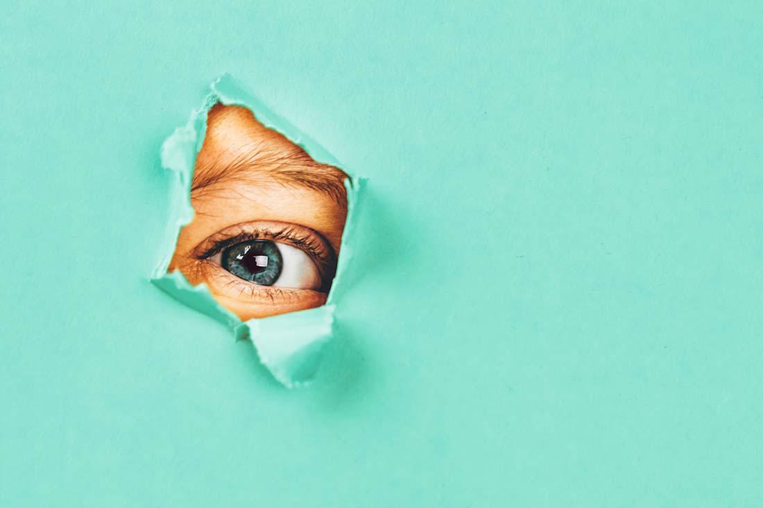 Durch ein Loch in einer blauen Papierwand schaut ein Auge.