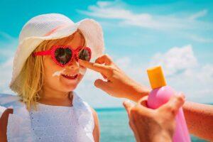 Ein Kind mit Sonnenbrille und Hut wird am Strand von der Mutter im Gesicht mit UV-Schutz eingecremt.