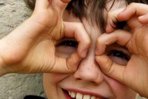Ein Junge formt die Finger zu einer Brille vor den Augen.