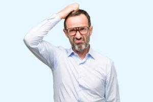 Ein älterer Mann mit Brille schaut zweifelnd und runzelt die Stirn.