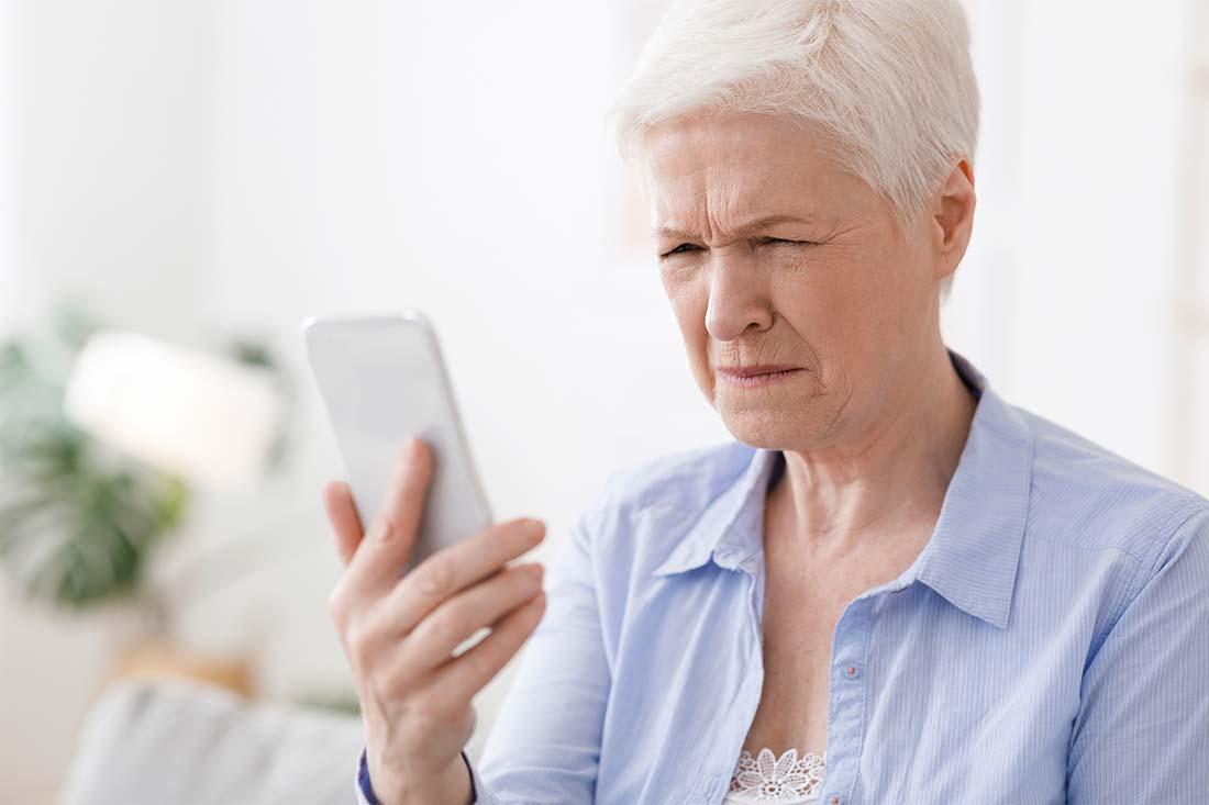 Eine ältere Frau schaut mit zusammengekniffenen Augen auf ihr Handy.