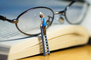 Eine Minitaurfigur steht auf einer kleinen Leiter, um eine Brille zu putzen.