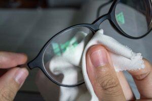 Brille wird mit einem Mikrofasertuch gereinigt.