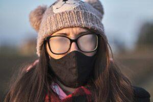 Die Brillengläser einer Frau, die einen Mundschutz und Mütze trägt, beschlagen sehr stark.