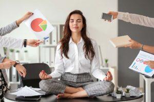 Eine Frau macht entspannt Yoga auf dem Schreibtisch, während ihr von allen Seiten neue Arbeitsaufträge entgegengestreckt werden.